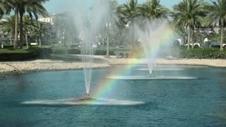 Fountains and colorful rainbow. Rainbow - meteorological phenomenon that is caused by reflection, refraction and dispersion of light in water droplets resulting in a spectrum of light appearing