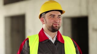 Funny builder on construction site make faces. Worker in hard hat stands on project site, looks at the camera and makes grimaces