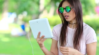 Girl communicates via tablet computer. Attractive woman with white tablet computer communicates through videochat. Female with tablet pc, she is in a merry mood