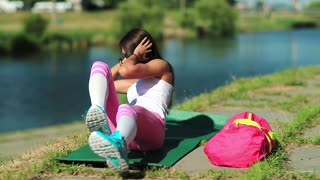 Girl doing physical exercises and pumps press. Sportswoman lies on green mat near the lake and train abdominal muscles. Woman goes in for sports, physical activity helps to burn up calories