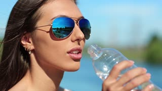 Girl in blue sun glasses drinks water. Attractive woman in sunglasses drinks clean water from a bottle