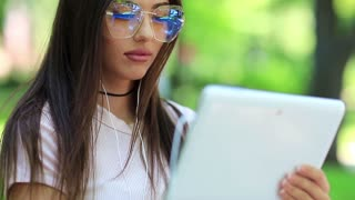 Girl in glasses uses tablet computer. Beautiful woman with white tablet pc. Female with tablet pc, she is in a merry mood