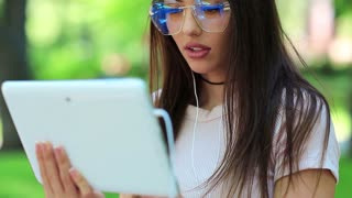 Girl in glasses uses tablet pc. Beautiful woman with white tablet computer, female with tablet pc