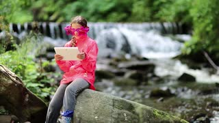 Girl in red jacket with white tablet pc sits on big stone near river in forest. Nice girl playing the game on his tablet computer. Girl in big glasses in shape of stars with tablet pc sits near brook