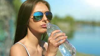 Girl in sun glasses drinks water. Attractive girl in glasses drinks clean water from bottle