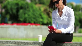 Girl in sunglasses with smartphone. Businesswoman with red cell phone drinks coffee
