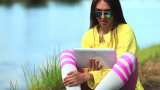 Girl sits near lake and talks via tablet computer. Attractive girl in sportswear with tablet computer communicates through skype or videochat