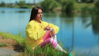 Girl sits on the grass near lake and drinks water. Attractive woman in sportswear drinks clean water from a bottle. Girl opens bottle of water and drink, female drinks soda water