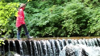 Girl walks on the brook in the wood. Girl in red jacket walks along small overflow dam on the river in the forest