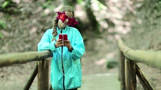 Girl with red smartphone stands on wooden bridge, listens to music, sings a song and dances. Attractive girl with big glasses in the shape of stars and with smartphone listens to music and dances