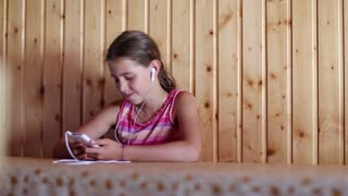 Girl with smartphone sits at table, listens to music and sings a song. Girl with white smartphone and earpieces listens to music, gesticulates and sings a song