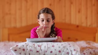 Girl with white tablet computer lies on the bed