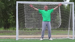 Goalkeeper guards football gate on soccer field. Active elderly athlete in football gate. Senior man stands in football goal. Physical activity helps to burn up calories