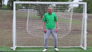Goalkeeper in green t-shirt guards football gate on soccer field. Senior man stands in football goal. Active elderly athlete in football gate. Physical activity helps to burn up calories