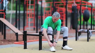 Grey-haired elderly athlete sits on the bench near outdoor gym and laces up his sneakers. Senior man laces up his jogging shoes near sports ground