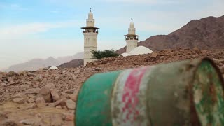 Iron barrel lies on the stony ground in defocus, mosque with two minarets on background in focus. Mosque and oil barrel. Old green rusty cask in mountain in Aqaba, Jordan. Empty barrel, lack of fuel