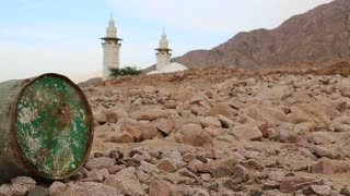Iron barrel lies on the stony ground, mosque with two minarets on background in defocus. Mosque and oil barrel. Old green rusty cask in mountain in Aqaba, Jordan. Empty barrel, lack of fuel