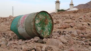 Iron barrel lies on the stony ground, mosque with two minarets on the background. Mosque and oil barrel. Old green rusty cask in mountain in Aqaba, Jordan. Empty barrel, lack of fuel