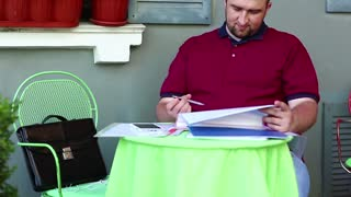 Irritable and nervous businessman sits at the table in restaurant and compares his documents. Angry man under a stress sits in summer cafe and works with business papers