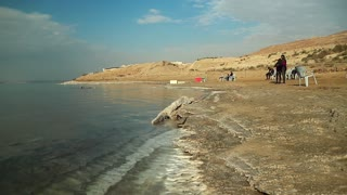 JORDAN, DEAD SEA, DECEMBER 8, 2016: People on the beach of Dead Sea. Mud therapy. Man swims in very salty water of Dead Sea, Hashemite Kingdom of Jordan