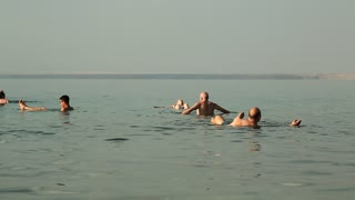 JORDAN, DEAD SEA, DECEMBER 8, 2016: People relax in very salty water of Dead Sea, Hashemite Kingdom of Jordan. People swim in Dead Sea