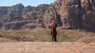 JORDAN, PETRA, DECEMBER 17, 2016: Jordanian in traditional clothes talks on cell phone, ancient Petra - historical and archaeological city in Hashemite Kingdom of Jordan