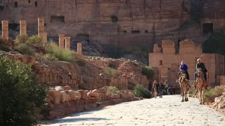 JORDAN, PETRA, DECEMBER 5, 2016: People rides on a camel near Temenos Gate and along The Colonnade Street in Petra - ancient city in Hashemite Kingdom of Jordan