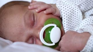 Little 2 weeks old newborn boy lies on the bed. Newborn baby sleeps with pacifier in mouth. Asleep newborn baby boy