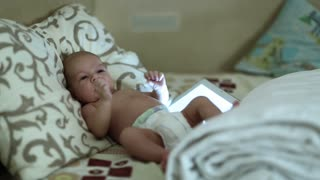Little baby lies on the bed with tablet computer. Active baby lies on the pillow, tablet computer lies next to him. Two months boy with tablet pc