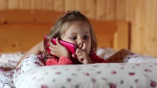 Little girl lies on the pillow and holds in hands mobile phone. Little girl with red cell phone lies on the sofa. Funny little girl with red smartphone lies on the bed and picks his nose