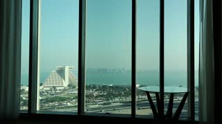 Man closes big window curtains in hotel room and go to bed. View of Doha - capital and most populous city in Qatar, Persian Gulf, Arabian Peninsula, Middle East
