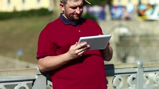 Man in baseball cap uses tablet computer, holds in hand his tablet pc. Businessman works with tablet computer