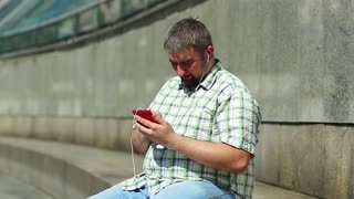 Man listens to music and moves. Businessman sits on the step and listens to music on his smartphone. Fat guy with red mobile phone