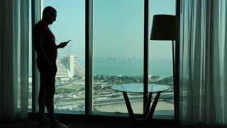 Man listens to music near big window in hotel room. View of coast of the Persian Gulf in Doha city, Qatar, Arabian Peninsula, Middle East