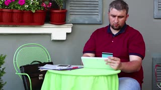 Man makes online purchase with credit card, shopping online with credit card. Businessman sits at the table in summer restaurant, holds in hand white tablet computer and blue credit card, enters data