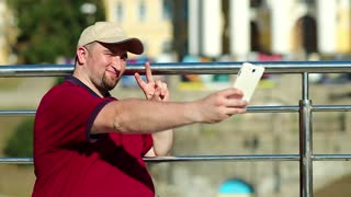 Man makes selfie on smartphone. Fat guy makes photos on his cell phone