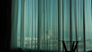 Man opens curtains in morning, raises his hands and stretch oneself. View of Doha - capital and most populous city in Qatar, Persian Gulf, Arabian Peninsula, Middle East
