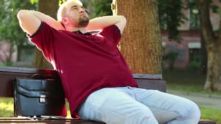 Man relaxes after hard working day. Businessman sits on bench in city park and rests