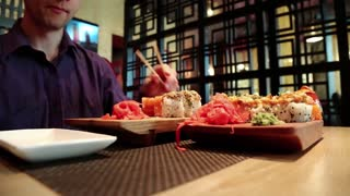 Man sits at the table in restaurant and eats japanese food. Boy in purple shirt eats sushi in japanese restaurant