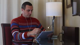 Man sits on chair at the table in hotel room and uses tablet computer. Concentrated man with tablet pc sits at the table