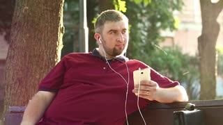 Man sits on the bench and listens to music. Businessman sits on the bench in city park and listens to music on his smartphone. Fat guy with white mobile phone sings a song