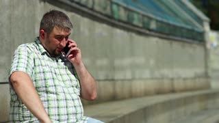 Man speaks on smartphone. Businessman sits on the steps and communicates via smartphone. Man talks on cell phone and gesticulates. Fat guy with red mobile phone in hand