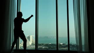 Man trains near big window in hotel room, shadow boxing. View of coast of the Persian Gulf in Doha - capital and most populous city in Qatar, Arabian Peninsula, Middle East