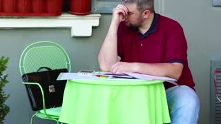 Man under a stress sits in summer cafe, smartphone, tablet pc and business papers lies on the table. Tired and stressed businessman sits at the table in summer restaurant
