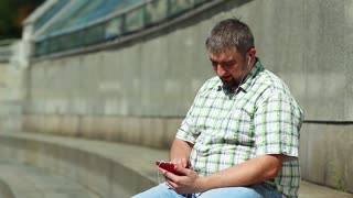 Man uses smartphone and listens to music. Businessman sits on the step and listens to music on his smartphone. Fat guy with red mobile phone