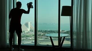 Man wipes big window in hotel room. View of Doha - capital and most populous city in Qatar, Persian Gulf, Arabian Peninsula