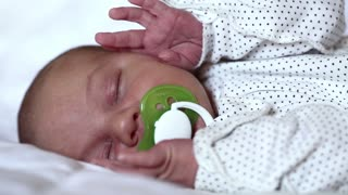 Newborn baby sleeps with pacifier in his mouth