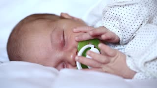 Newborn baby sleeps with pacifier in mouth