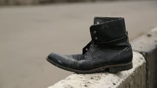 Old black shoe near the road. Boot near the highway, traffic violation and road accident. Do not run across road