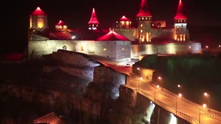Old castle with red illumination at night, is former Ruthenian-Lithuanian castle and a later Polish fortress, located in historic city of Kamianets-Podilskyi, in historic region of Podolia in Ukraine